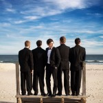 Groomsmen standing on steps at the beach